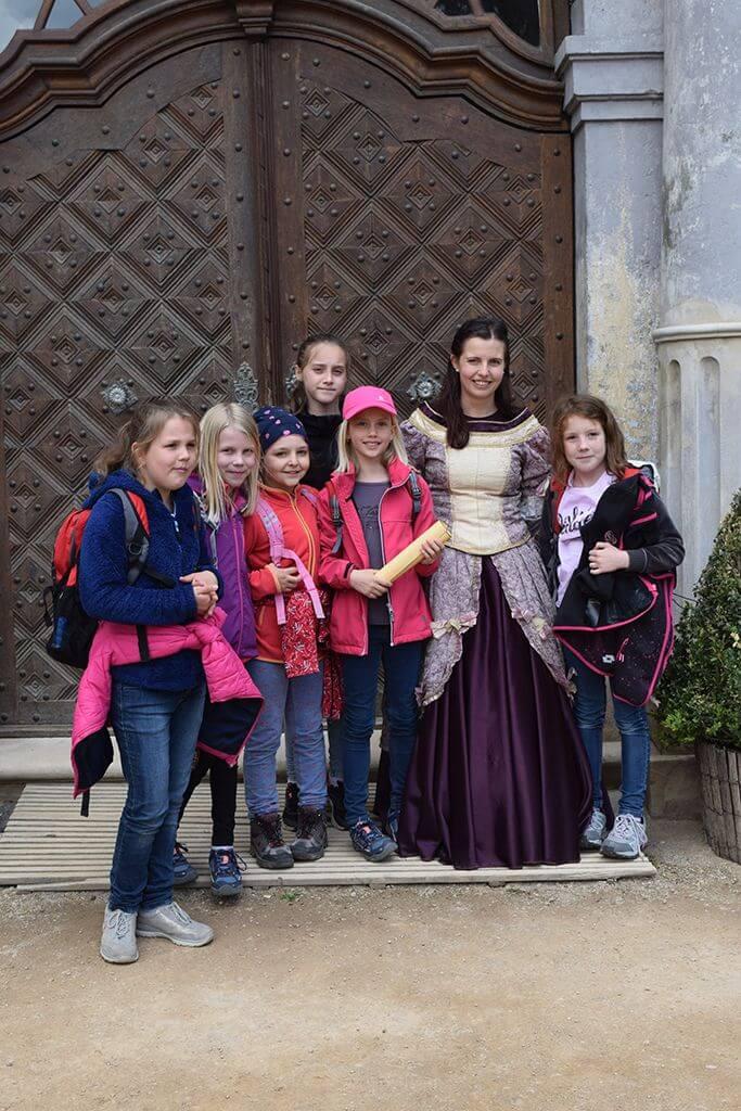 Děti s komtesou u vstupu do zámku na dětskou prohlídku