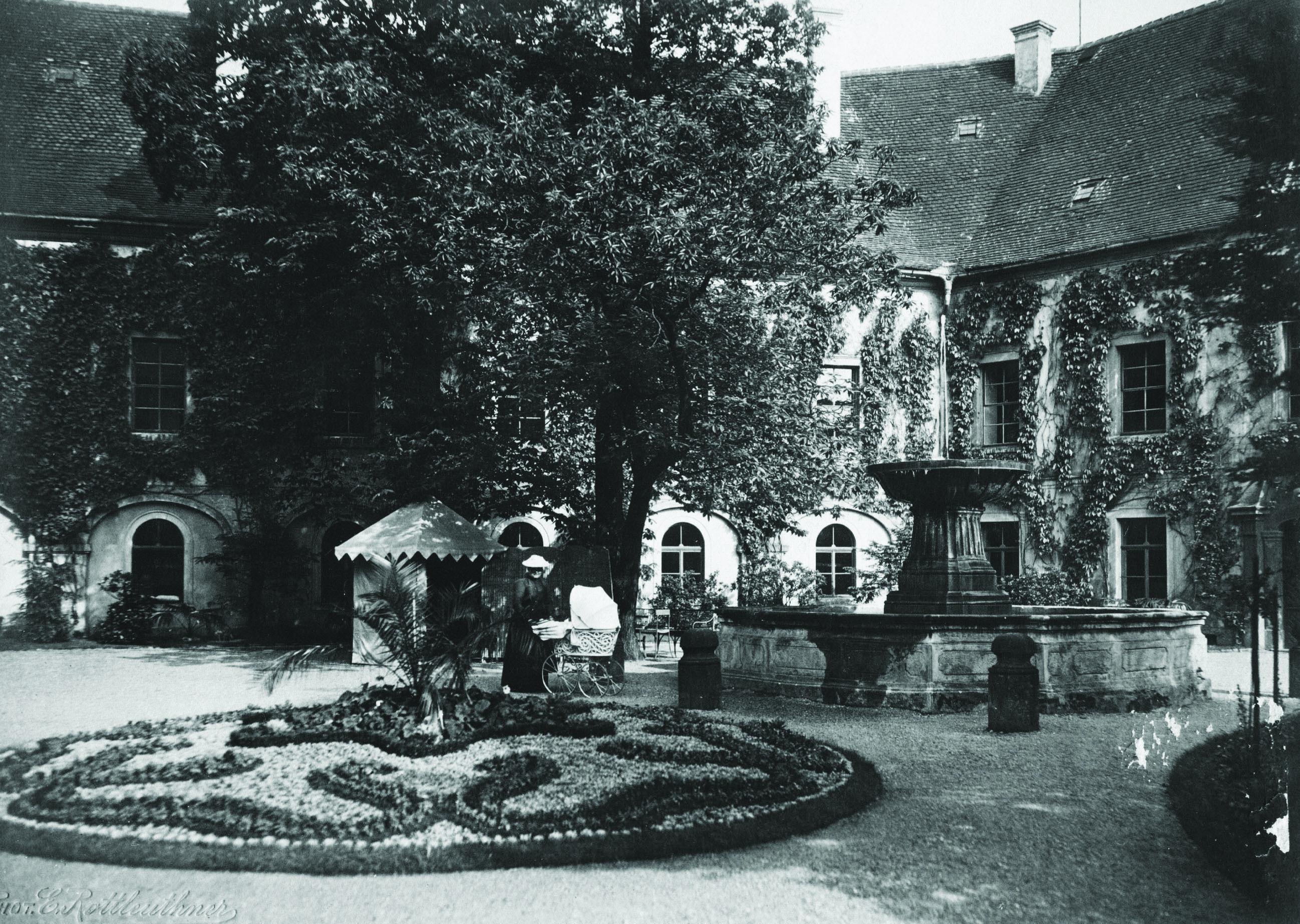 Kněžna s kočárkem na nádvoří zámku, historická fotografie