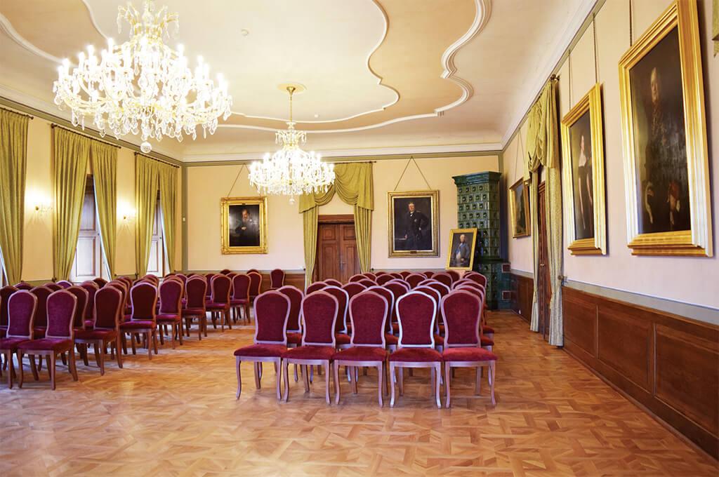 Rohový sál s obrazy portrétů a kachlovými kamny