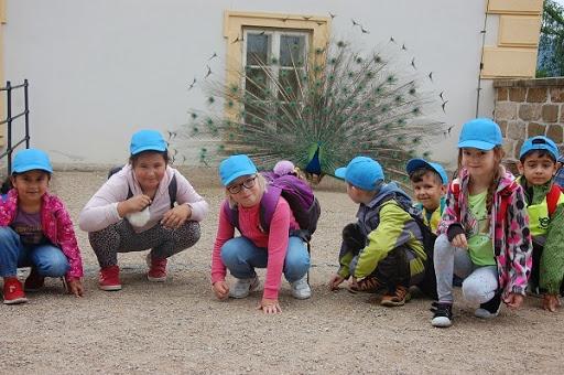 Děti s pávem na nádvoří zámku